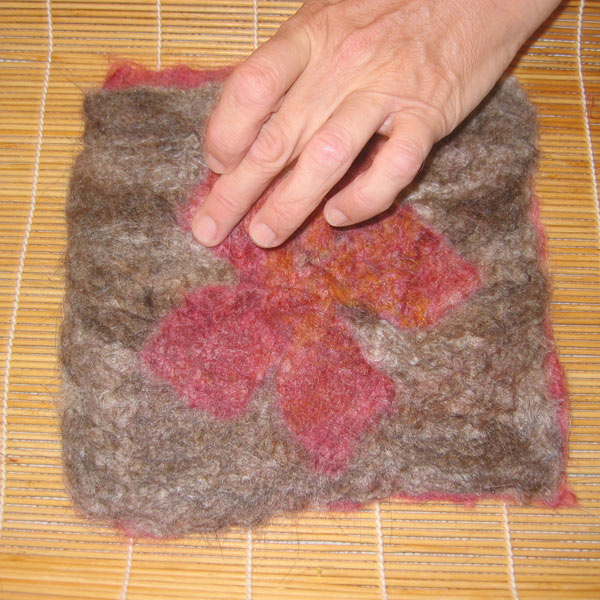 A piece of felted material that has a a coloured edge and a flower graphic in the middle