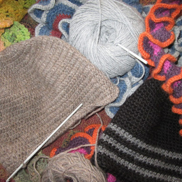 A collage of knitted clothing including a beanie, wool and rope